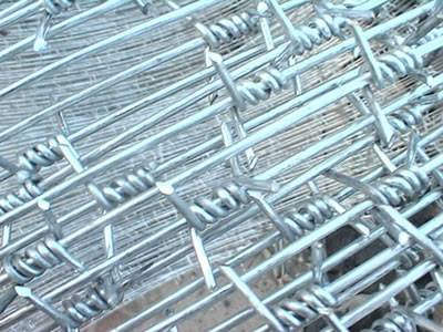 A roll of galvanized single twist barbed wire and a detail of single strand and twist.