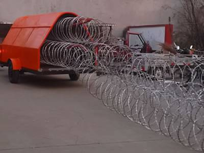 An orange razor wire trailer is stretching concertina razor wire. And the wire has been stretched for a long distance.