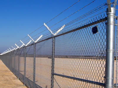Chain link security fence combined with barbed wire used in large construction site.