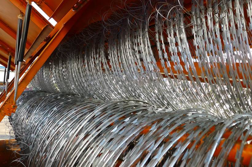 Three coils of concertina razor wire with clips and tie wire in orange trailer.