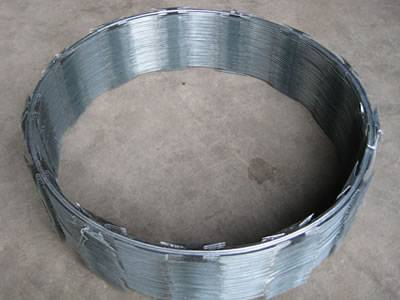 A compressed coil of galvanized concertina razor wire is on the floor.