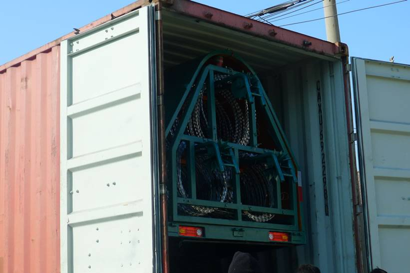 A green razor wire trailer with triple strand of razor wire has been in a red color container.