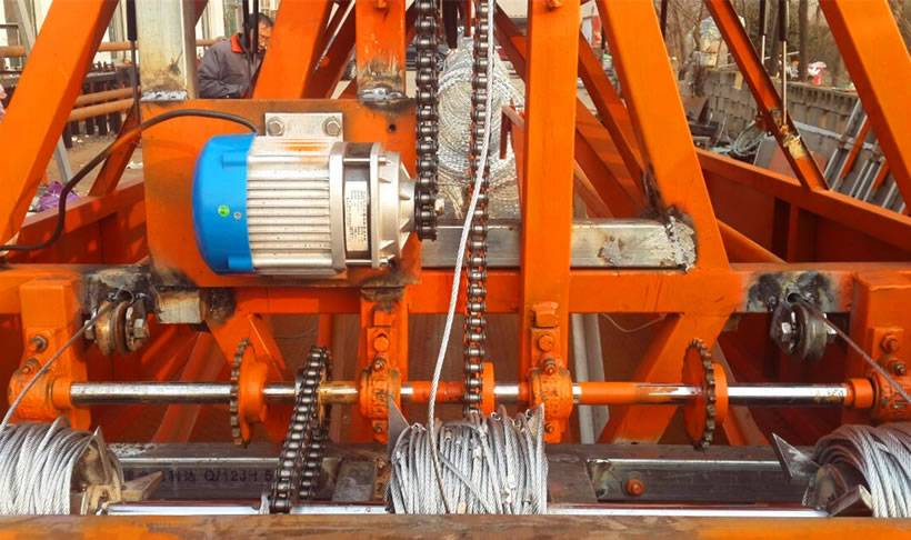 A headstock of an orange trailer deployment with motor, chain, gear and steel rope mesh.