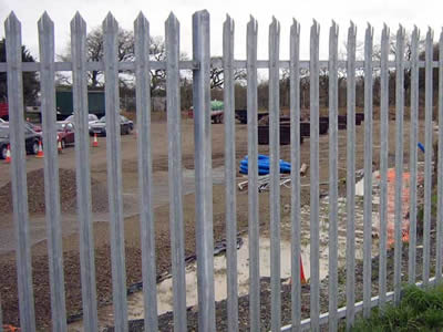 A galvanized security palisade fence surrounding a construction site.