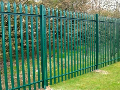 A forest is separated from the outside world by a green PVC coated palisade fence.