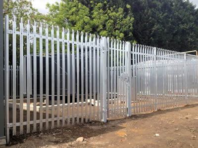 A galvanized security palisade fence surrounding a voltage box.