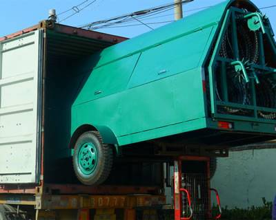 A green razor wire trailer with a half is entering into the container.