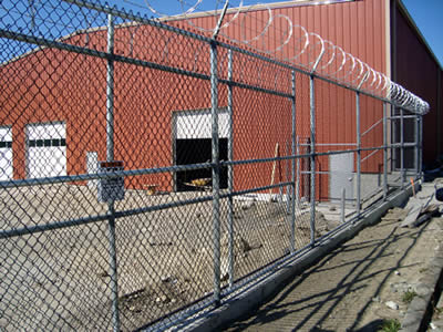 Chain link security fence combined with barbed wire and razor wire is used in factory.