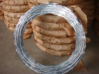 Many coils of razor wire is packed with kraft paper and one coil without packing.