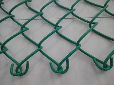 A part of chain link fence with twist ends is placed on the floor.